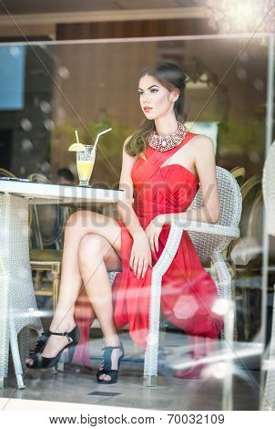 Fashionable attractive young woman in red dress sitting in restaurant, beyond the windows. Beautiful