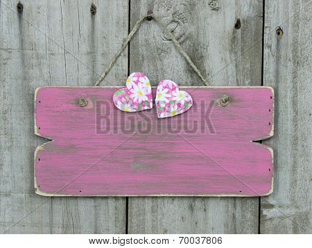 Blank rustic pink sign with daisy hearts hanging on wooden door