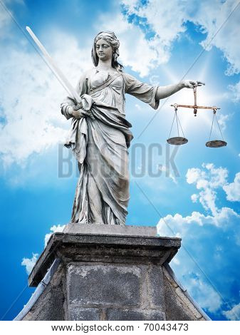 An image of a beautiful justitia statue in front of a blue sky