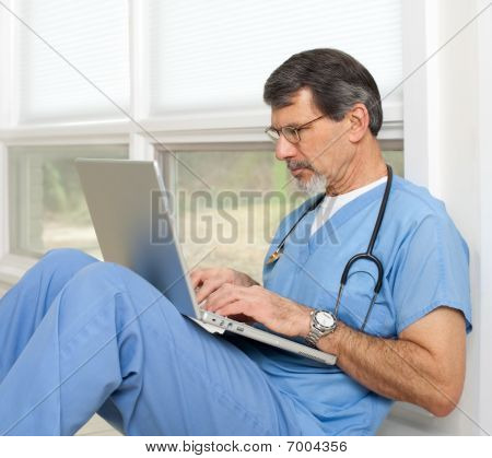 Doctor Reviewing And Researching On Laptop Computer