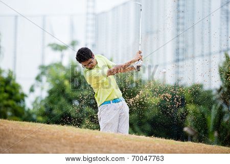 Male golfer hitting golf ball out of a sand trap with sand