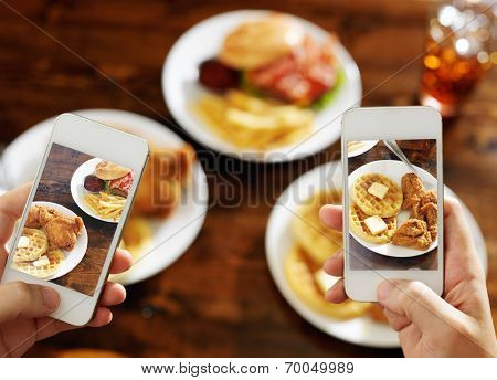 two friends taking photo of their food with smart phones
