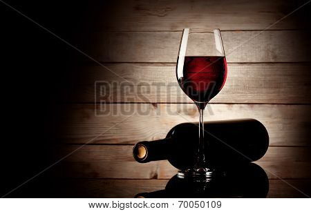 Glass Of Red Wine And Bottle Lying On Its Side