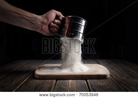 Hand Sifts The Flour Through A Sieve.