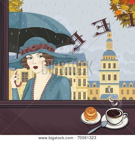 Portrait of a young woman with an umbrella in the window of a coffee-house in the rainy autumn day.