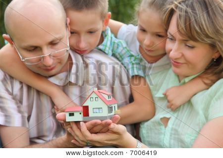 family with two children is keeping wendy house in their hands and looking at it