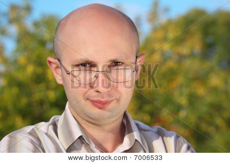 handsome man with glasses in fall park looking at camera