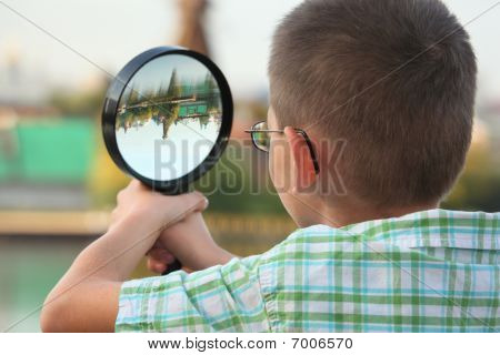little boy is looking through magnifier in early fall park. focus on boy's ear.