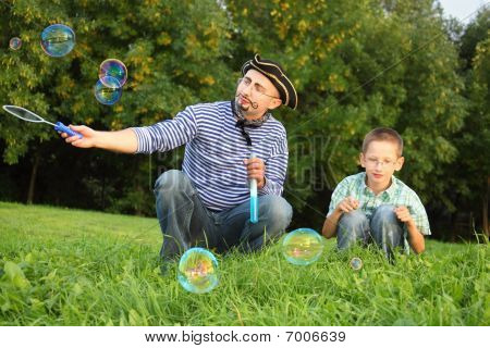 man with drawed beard and whiskers is blowing soap bubbles. his son is looking on little soap bubble