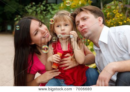 Little girl in red dress with father and mother starts up soap bubbles in park in warm afternoon.