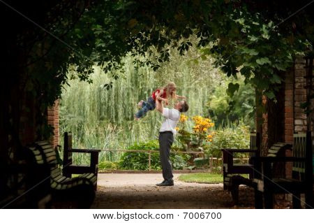 Father and daughter in summer garden in plant tunnel. Man plays with girl lifting her on hands