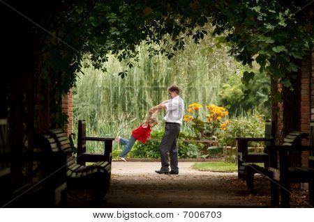 Father and daughter in summer garden in plant tunnel. Man plays with girl turning her on hands