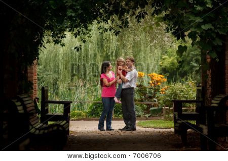 Parents and the little girl in summer garden in plant tunnel. Man holds girl on hands.