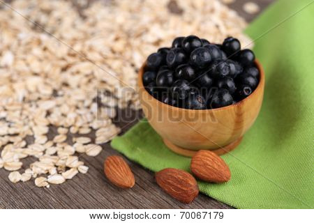 Little round bowl of bilberries on a green napkin with scattered oatmeal