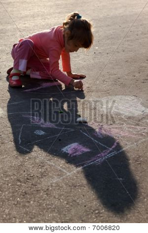 girl sits on concrete asphalt square road. girl draws painting line sun house tree a chalk on asphal