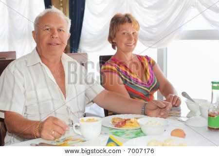 Smiling Elderly Married Couple Having Breakfast At Restaurant Near Window