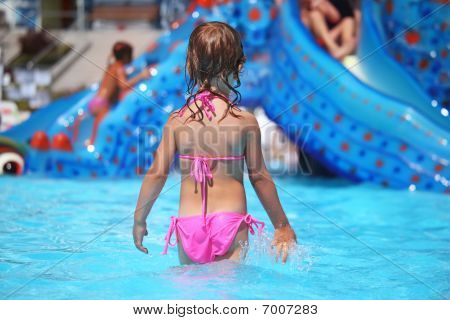 Little Girl Standing In Pool In Aquapark, Standing Back
