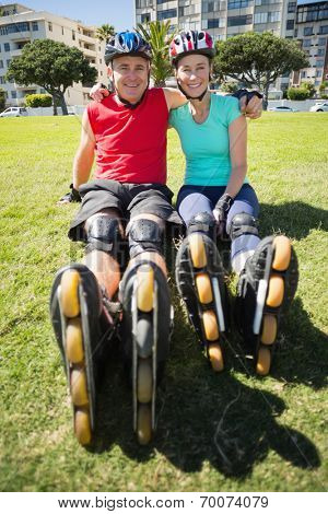 Fit mature couple wearing roller blades on the grass on a sunny day