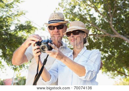 Happy senior couple looking at their camera on a sunny day