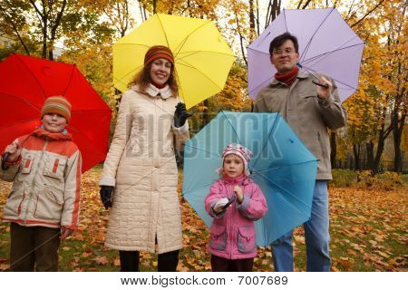 Family from four persons in autumn park with multi-coloured umbrellas.