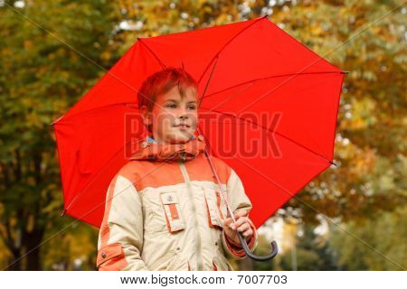 Portrait of boy in autumn park. With big red umbrella. Horizontal format