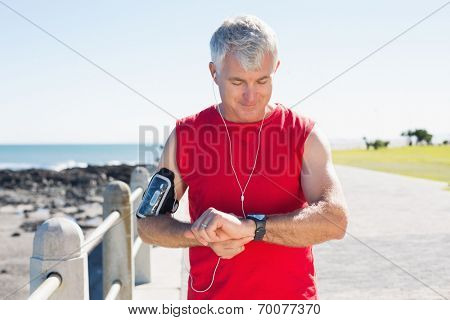 Fit mature man checking the time on the pier on a sunny day
