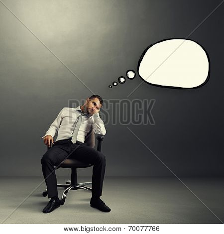 bored businessman sitting on the chair with empty speech bubble over grey background
