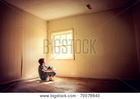 Boy sitting alone looking out the window with rays of lighting s