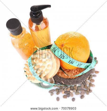 Fresh orange, tapeline, plate,bast, brush and sea stones scattered around on white background isolated