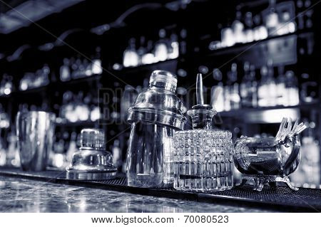 Bartender tools sitting on bar counter, toned image