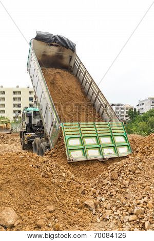 Dump Truck Dumps Its Load Of Rock And Soil On Land