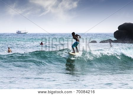Silhouette Young Boy Surfing On Wave.