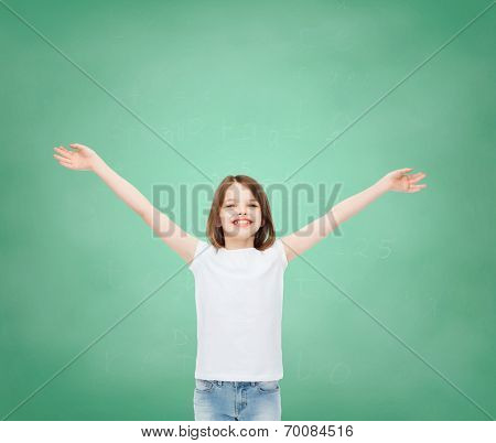 advertising, gesture, education, childhood and people - smiling girl in white t-shirt with stretched out arms over green board background