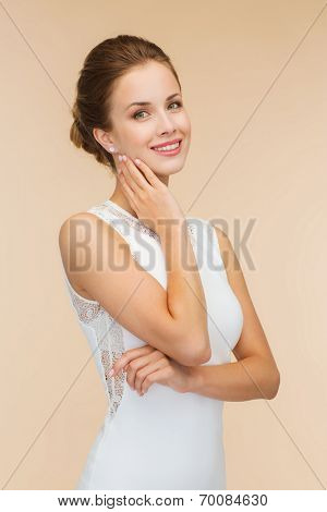engagenment, celebration, wedding and happiness concept - smiling woman in white dress wearing diamond ring over beige background