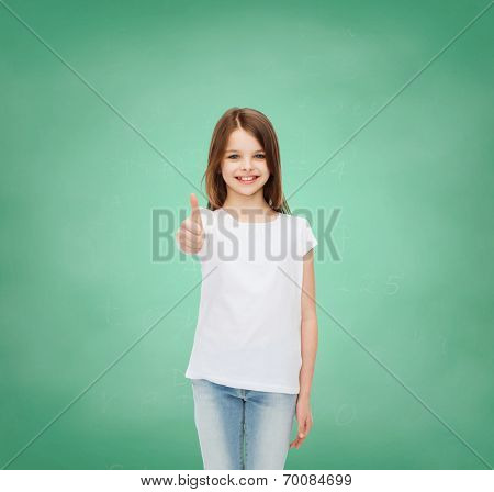 advertising, gesture, education, childhood and people - smiling little girl in white t-shirt showing thumbs up over green board background