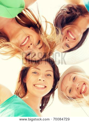 summer holidays and vacation concept - faces of girls looking down and smiling