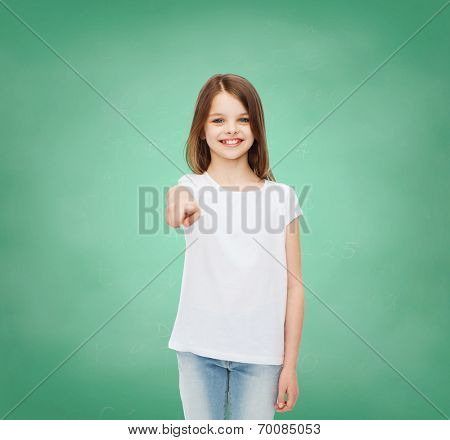 advertising, gesture, school, education and people - smiling little girl in white blank t-shirt over green board background