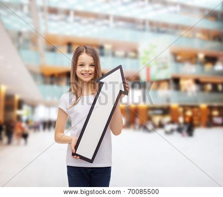 advertising, direction, consumerism and childhood concept - smiling little girl with white blank arrow pointing up over shopping center background
