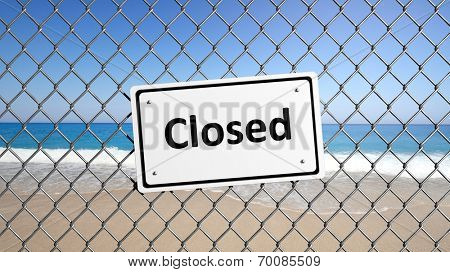 Metal fence with sign Closed in front of a beach