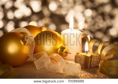 Beautiful golden Christmas background with candles, baubles and ribbons on bokeh