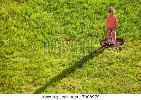 little girl is standing on water drain hatch in grass field. girl in right upper corner