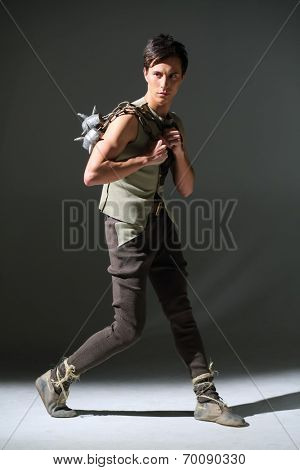 Handsome young man in a costume with a mace posing in studio