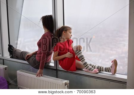 Woman and girl sitting on the windowsill of a large window and looking out onto the city