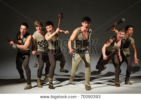 Group of strong young men running and screaming with maces in their hands