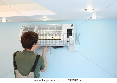 Young worker installs air conditioner in the room with blue walls
