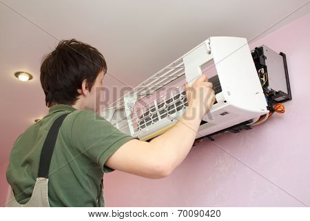 Worker installs grid on the air conditioner in the new apartment