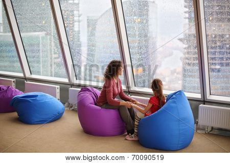 Woman with daughter sitting holding hands and looking into the large window on the city