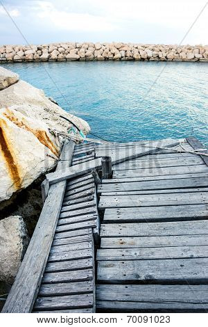 Damaged Wooden Pier With Rock