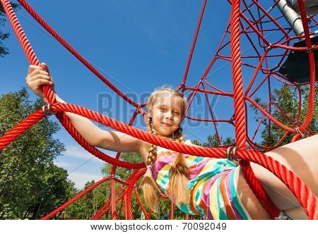 Girl with two braids sits on ropes of red net