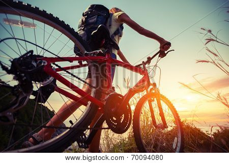 Hiker with bicycle watching sunset